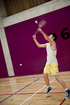 Photo of a person playing badminton in the multipurpose area