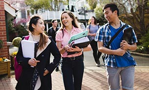 Three first-year students walking through campus