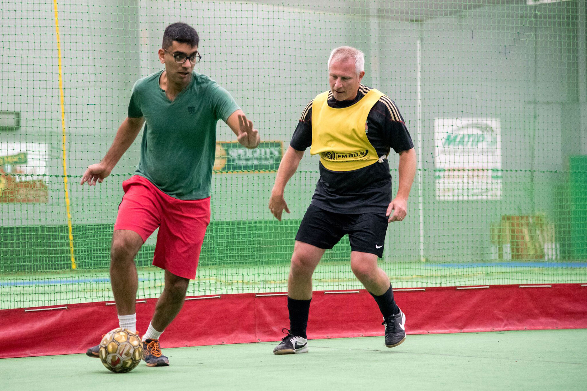 Naveen and Paul competing in staff versus student soccer (2017)