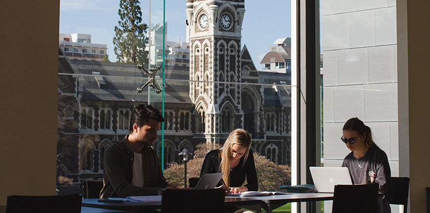 Students studying across the river from the Clocktower Building at University of Otago