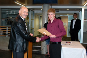 Class of 1979 Undergraduate Medical Scholarship recipient Blake Henley receiving his award from Professor Mike Hunter.